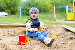 Lovely baby playing with sand on playground. Lovely 21 months baby playing with sand on playground in summer Stock Photos