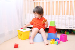 Lovely baby plays toys sitting on potty. Lovely baby boy plays toys sitting on potty royalty free stock photos