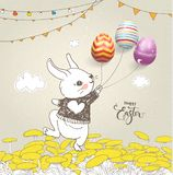 Lovely baby rabbit dressed in jumper holding colorful eggs on threads, floral field, flag garlands and Happy Easter Stock Images