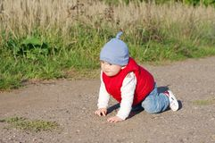 Lovely baby in red waistcoat creeps on ground Stock Photos
