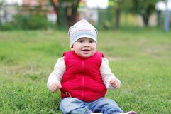 Lovely baby in red waistcoat sitting on grass outdoors Stock Photography