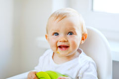 Lovely baby sitting in baby chair Stock Photos