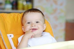 Lovely baby sitting on baby chair. On kitchen Royalty Free Stock Images