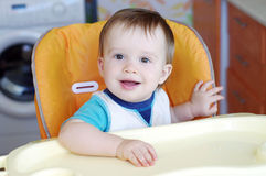Lovely baby sitting on baby chair on kitchen Stock Photography