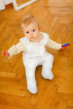 Lovely baby sitting on floor Stock Images