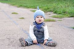 Lovely baby sitting outdoors on the ground. Lovely baby age of 11 months sitting outdoors Royalty Free Stock Images