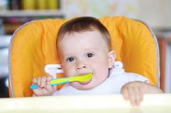 Lovely baby with spoon. On kitchen Royalty Free Stock Photo