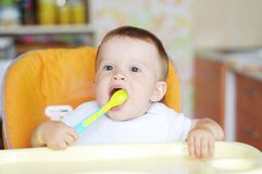 Lovely baby with spoon on kitchen Royalty Free Stock Photo