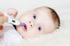 Lovely baby take temperature with electronic thermometer Royalty Free Stock Image