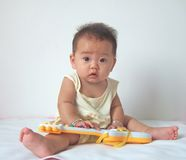 Lovely baby and toy guitar royalty free stock photos