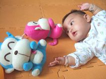 Lovely baby and toy monkeys royalty free stock photography
