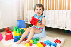 Lovely baby with toys sitting on potty. Lovely baby boy plays toys sitting on potty stock photo