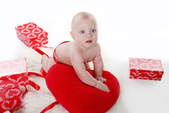 Lovely baby with Valentine's heart and gifts boxes Royalty Free Stock Photography