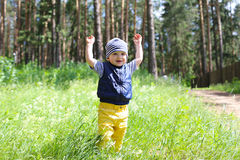Lovely baby walking in forest against flowers Stock Image