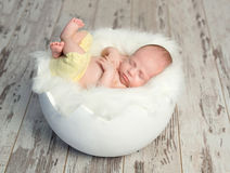 Lovely baby in yellow pants on white cot like shell. Lovely sleeping baby in yellow pants with legs up on white cot like egg shell Stock Photo