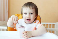Lovely baby with youghourt Stock Images