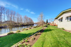 Lovely back yard with grass and river. Stock Photo