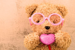 Lovely bear doll wearing pink glasses and holding heart sh Stock Photography
