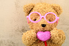Lovely bear doll wearing pink glasses and holding heart sh Royalty Free Stock Photos