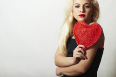 Lovely Beautiful Blond Woman with Red Heart. Beauty Girl. Show Love Symbol. Valentine's Day. Black Dress Stock Photo