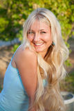 Lovely beautiful blonde woman outdoor. Lovely beautiful blonde woman against sunny outdoor greenery royalty free stock images