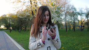 Lovely and beautiful brunette girl in coat uses the phone standing in a Park. stock video