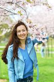 Lovely Beautiful Caucasian Woman Standing Posing on the Background of Blooming Japan Cherry stock photo