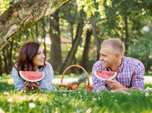 Lovely beautiful couple eating watermelon and lying on the grass in the summer park. Royalty Free Stock Image