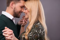 Lovely beautiful couple. Half-length portrait of lovely happy smiling couple standing with closed eyes facing each other dancing enjoying the moment they are Stock Photo