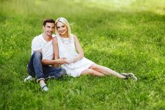 The lovely couple in love sitting on green grass. Royalty Free Stock Photos