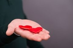 Lovely beautiful couple. Selective focus on two little red hearts lying on the hand on background Royalty Free Stock Photos