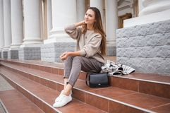 Lovely beautiful stylish woman sitting on street stairs with legs crossed stock photo