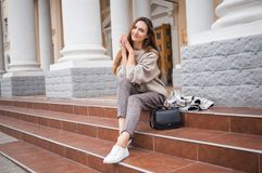 Lovely beautiful stylish woman sitting on street stairs with legs crossed stock photos