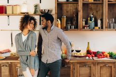 Lovely black couple standing in cozy kitchen. Lovely couple standing together in cozy kitchen, looking at each other, copy space stock images
