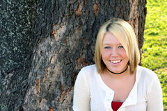 Lovely Blond. Smiling young blond woman, standing in front of a large tree outdoors Stock Photo