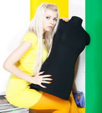Lovely blond girl with black dummy sitting Stock Photo