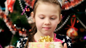 Lovely blond girl with a pink bow in her hair, in a beautiful elegant dress, looks with curiosity at her Christmas gift stock video footage