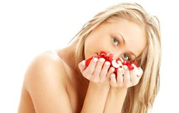 Lovely blond in spa with red and white rose petals Stock Photography