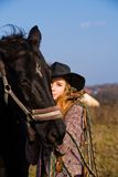 Lovely blond woman in a hat standing by horse. In a field Stock Image