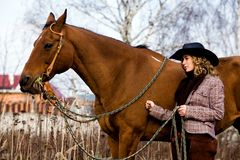 Lovely blond woman in a hat standing by horse. Outdoors Stock Photography