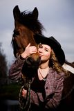 Lovely blond woman in a hat standing by horse. Outdoors Stock Photos