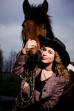Lovely blond woman in a hat standing by horse. Outdoors Royalty Free Stock Photo