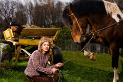 Lovely blond woman sitting by horse. Outdoors Royalty Free Stock Image