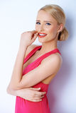 Lovely blond woman smiling while posing on white Stock Images