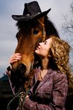 Lovely blond woman standing by horse. Outdoors Royalty Free Stock Images