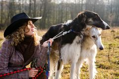 Lovely blond woman with two dogs in a field. Lovely blond woman in hat with two dogs in a field Royalty Free Stock Photos
