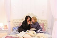 Best female friends watch news on Internet on smartphone and cha stock images