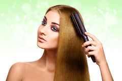 Lovely blonde combing hair and looking away with blue eyes Royalty Free Stock Images