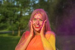 Lovely blonde girl having fun with colorful dry paint at the park. Concept for festival Holi. Lovely blonde woman having fun with colorful dry paint at the park royalty free stock images
