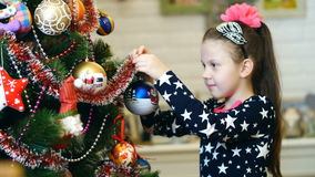 Lovely blonde girl with a pink bow in her hair and in a beautiful festive dress decorates a Christmas tree with bright stock video